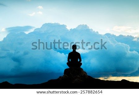 Silhouette of the meditating person against an approaching thunder-storm - stock photo