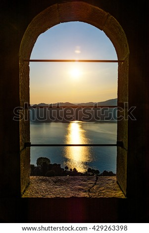 Silhouette of the mountains and the town of Arona in Italy at sunset and water. View from the castle window - stock photo