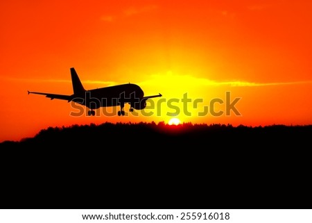 Silhouette of the plane landing above the sunrise - stock photo