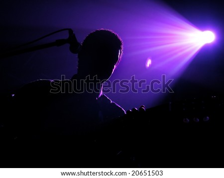 Silhouette of the playing guitarist under beams of violet light