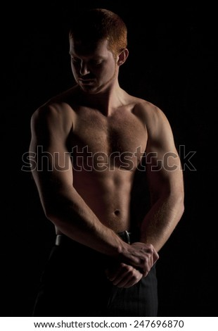 Silhouette of the strong young naked muscleman in the dark. Perfect body studio shot - stock photo