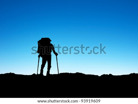 Silhouette of the tourist on background blue sky. Active life