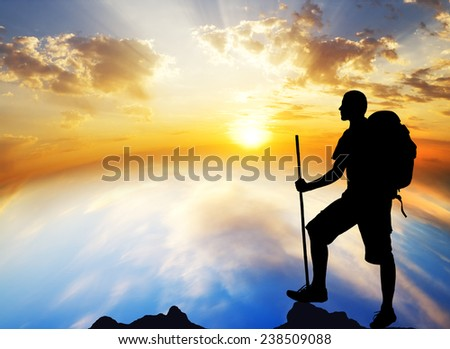 Silhouette of the tourist on sundown background. Sport and active life - stock photo