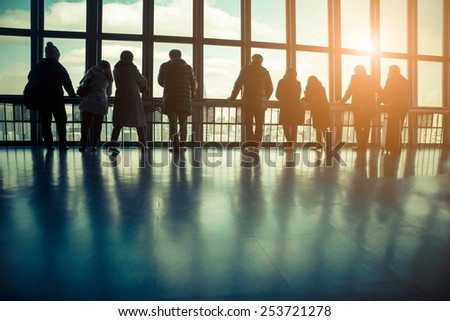 Silhouette of the tourists at transparent viewing observatory - People watching at window at sunset - Travelers waiting flight at airport - stock photo