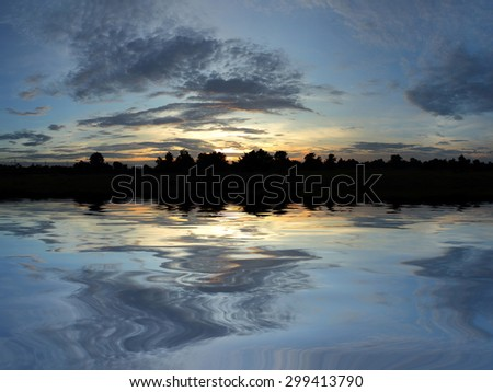 Silhouette of the tree during sunset with colorful sky and beautiful water reflection - stock photo