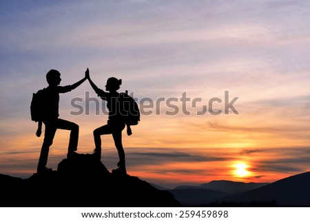 Silhouette of the two people man girl success on the peak of mountain. Sport and active life sunset landscape - stock photo