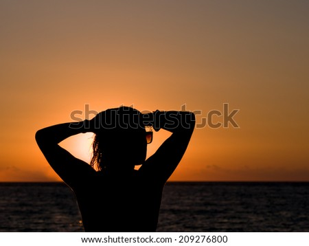 Silhouette of the woman standing at the beach during beautiful sunset. - stock photo