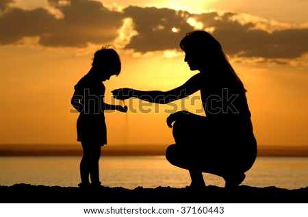 Silhouette of the women to pour sand in hand child on sundown