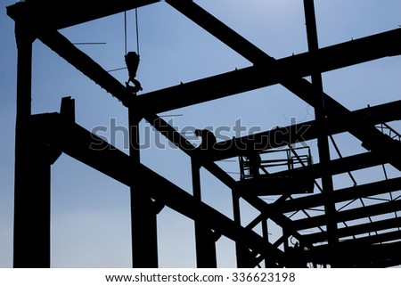 Silhouette of the workers dissembling industrial constructions. - stock photo