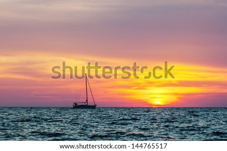 Silhouette of the yacht at sunset sea background