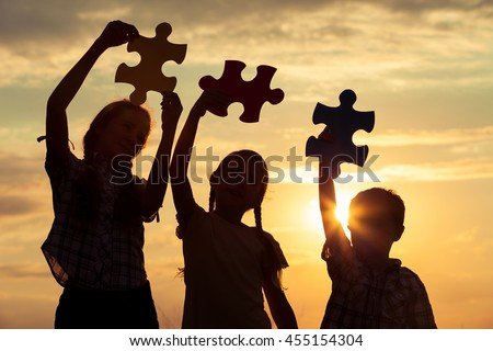 Silhouette of three happy children which playing on the field at the sunset time. They having fun on the nature. Concept of the kids are ready to go to school. - stock photo