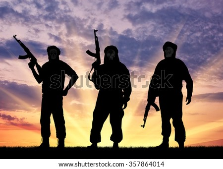 Silhouette of three terrorists with a weapon against a background of sunset