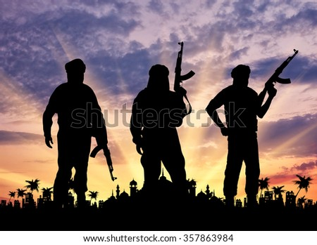 Silhouette of three terrorists with weapons against the sunset and the town hall with palm trees