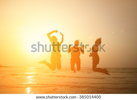 Silhouette of three young girls  jumping with hands up on the beach at the sunset,motion - stock photo