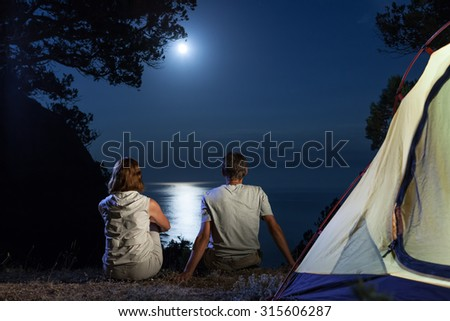 Silhouette of tourist couple near tent looking at moon at night