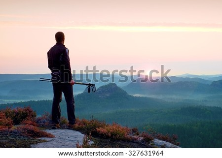 Silhouette of tourist guide with poles in hand. Hiker with sportswear stand on view point above misty valley. Sunny spring daybreak in rocky mountains.