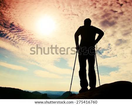 Silhouette of tourist with poles in hand. Hiker stand on rocky view point above misty valley. Sunny spring daybreak in rocky mountains. - stock photo