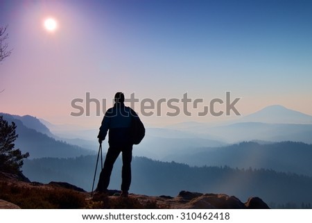 Silhouette of tourist with poles in hand. Hiker with sporty backpack stand on rocky view point above misty valley. Sunny spring daybreak in rocky mountains. - stock photo