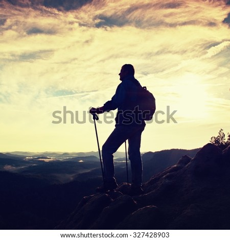 Silhouette of tourist with poles in hand. Hiker with sporty backpack stand on rocky view point above misty valley. Sunny spring daybreak in rocky mountains.