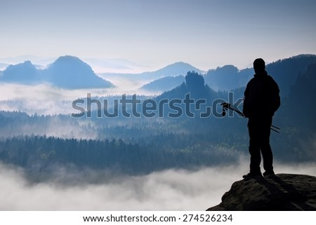 Silhouette of tourist with poles in hand. Sunny spring daybreak in rocky mountains. Hiker with sporty backpack stand on rocky view point above misty valley.