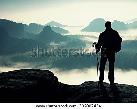 Silhouette of tourist with poles in hand. Sunny spring daybreak in rocky mountains. Hiker with sporty backpack stand on rocky view point above misty valley.  - stock photo