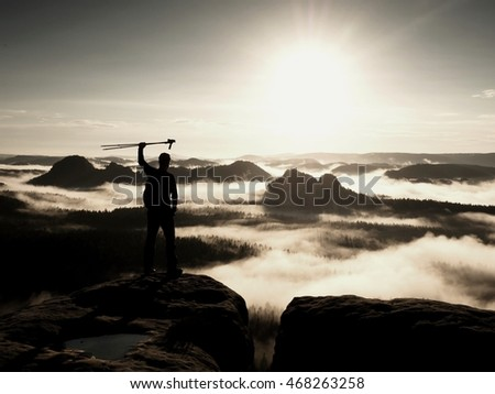 Silhouette of tourist with poles in hand. Sunny spring daybreak in rocky mountains. Hiker with sporty backpack stand on rocky view point above misty valley. Raised contrast