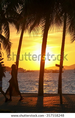 Silhouette of tourists walking on the street of Pttaya beach, Thailand, with sunset over the sea and row of palm trees in the background. - stock photo