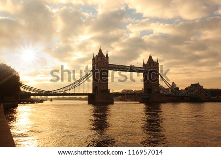 Silhouette of Tower Bridge against morning sunrise in London, England - stock photo