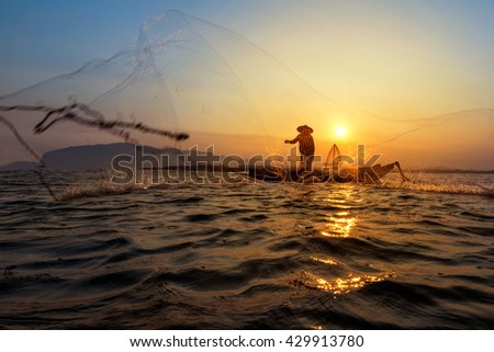 Silhouette of traditional fishermen throwing net fishing lake at sunrise time.(The casting people living along the River) - stock photo
