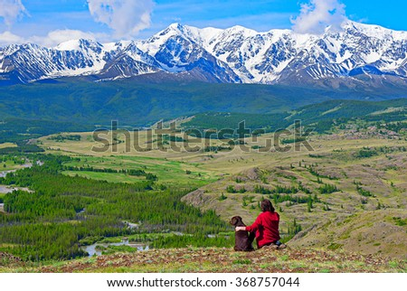Silhouette of traveler with a dog in the mountains - stock photo