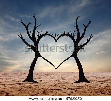 Silhouette of tree branch making the heart symbol in a barren landscape against a surreal evening sky.  - stock photo