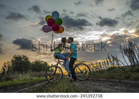 Silhouette of two beautiful people looking each other Young couple sitting at one bicycle Girl holding colorful balloons on sunset cloudy sky trees park background Copy space for inscription Kiss lips - stock photo