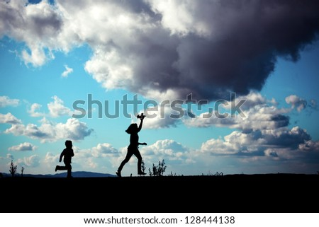 silhouette of two children running with a toy against a dramatic sky