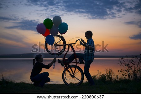 Silhouette of two couple Man sitting at one bicycle Woman holding and give colorful balloons on sunset cloudy sky on Water in lake background Copy space for inscription Pair on date  Birthday party