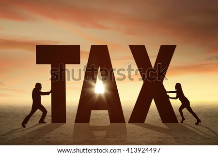 Silhouette of two entrepreneurs pushing a tax word at sunset time
