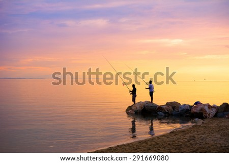 Silhouette of two fishermen fishing in the sea at sunset - stock photo