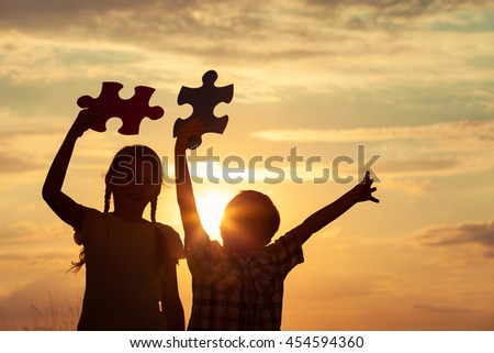 Silhouette of two happy children which playing on the field at the sunset time. They having fun on the nature. Concept of the kids are ready to go to school. - stock photo