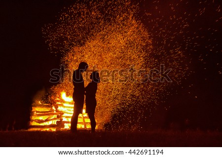 Silhouette of two loving people on love in front of fire. Original marriage or background wallpaper - stock photo