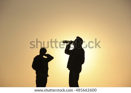 Silhouette of two men, with one man drinking beer from a bottle. Concept: Silhouette, Alcoholism, Consumption