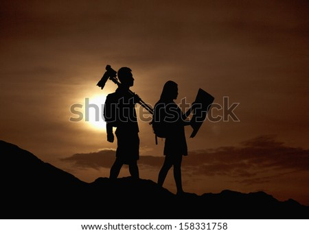 Silhouette of two people hiking and carrying camera and a map at sunset