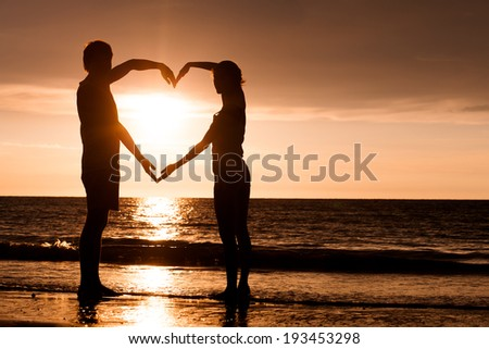 silhouette of two people in love at sunset - stock photo