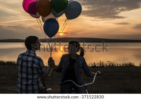 Silhouette of two people on romantic date looking each other Young couple sitting at bicycle Girl holding colorful balloons on sunset cloudy sky trees park background. Copy space for inscription. - stock photo