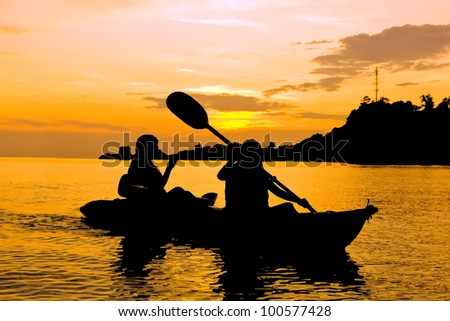Silhouette of Two person kayaking in the sea at sunset in Koh Chang Thailand - stock photo