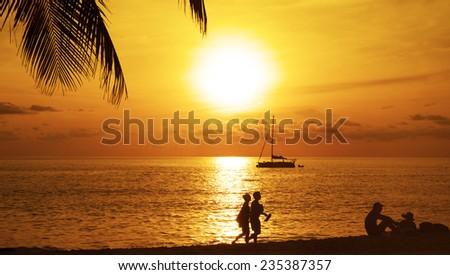 Silhouette of Two Romantic couple enjoying a beach walk along sun set beach and sit at sunset sand against water texture and sky with clouds evening background Empty copy space for inscription