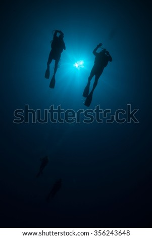 Silhouette of two scuba divers - stock photo
