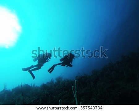 Silhouette of two SCUBA divers above a reef, with the brightness of the surface above
