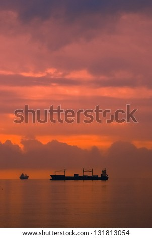 Silhouette of two ships in the ocean at sunset