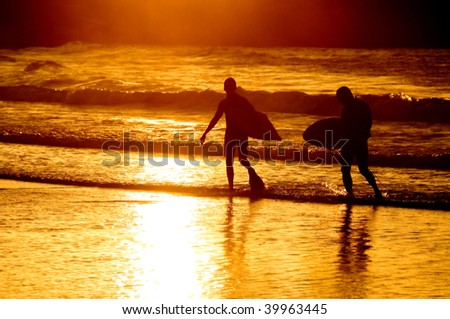 Silhouette of two surfer at yellow sunset - stock photo