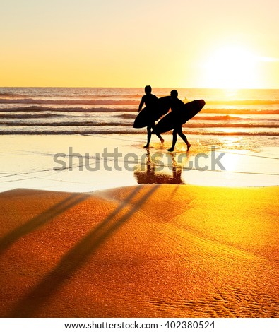 Silhouette of two surfer on the beach at sunset. Portugal  - stock photo