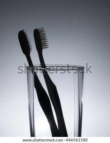 Silhouette of two toothbrushes in glass - stock photo